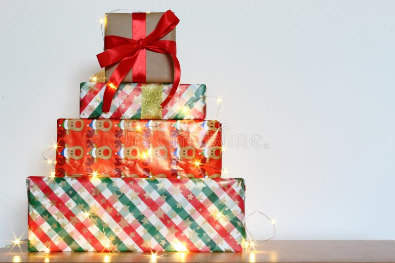 Big pile of colorful wrapped gift boxes isolated on wood table and white background. Mountain gifts. stock image