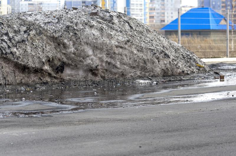 Big Pile of Dirty Melting Snow in a Parking Lot with Puddles and trash Collected over Winter Time. Warm Spring Day.  stock photography