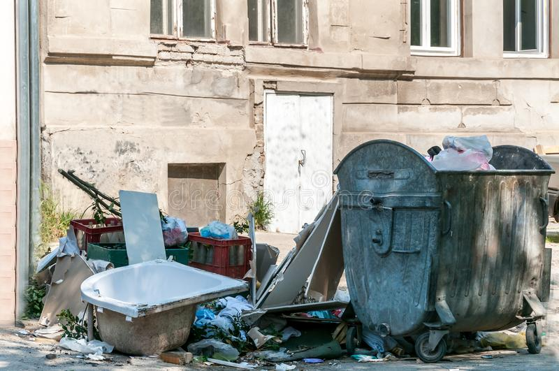 Big pile of garbage and junk dumped on the street near dumpster can.  royalty free stock image