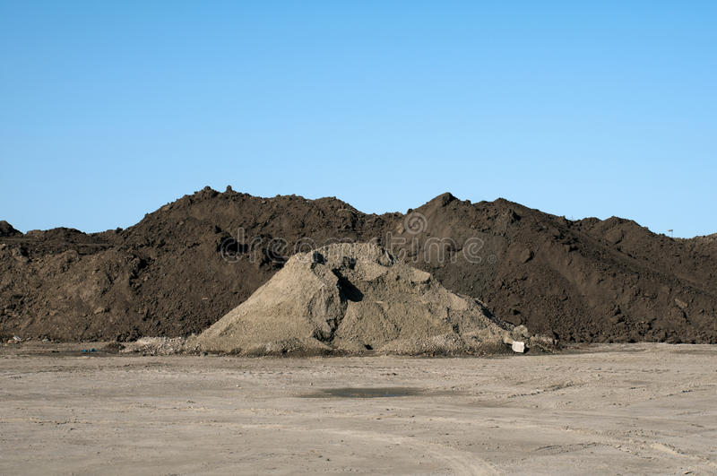 Big pile of soil. Against a blue sky stock photography