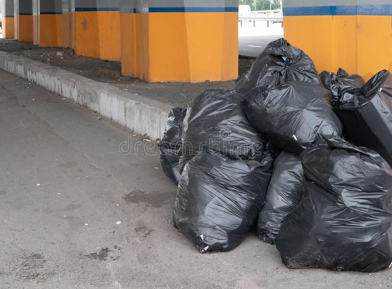 Big pile stack of plastic trash garbage bags. Under the bridge on city street. depict environment pollution or ecology catastrophe royalty free stock photos