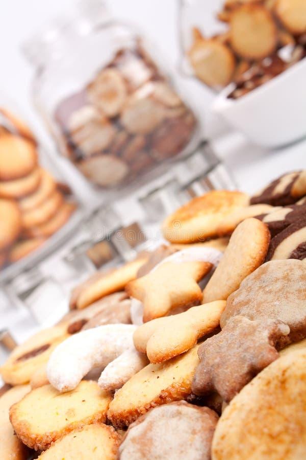 A big pile of various cookies with three cookie ja