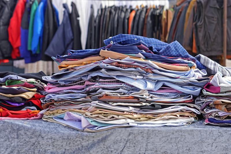 Second hand clothing. Big piles of second hand clothing at flea market royalty free stock photos
