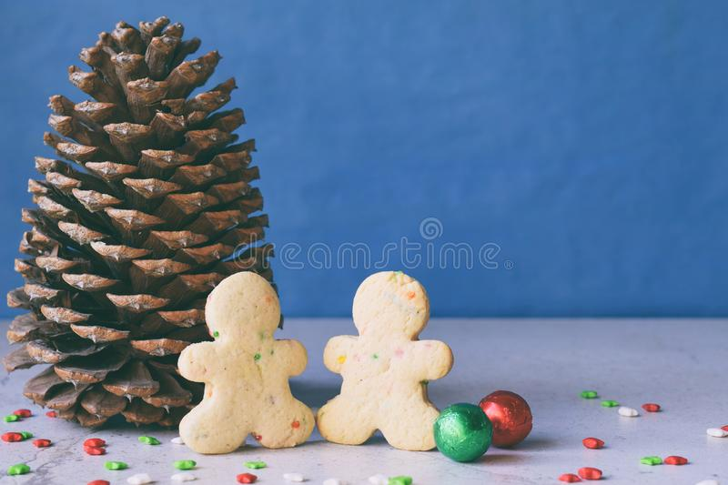 Big pine cone, gingerbread men and gifts on blue background. Happy New Year and Merry Christmas concept. Copy space.  stock photo