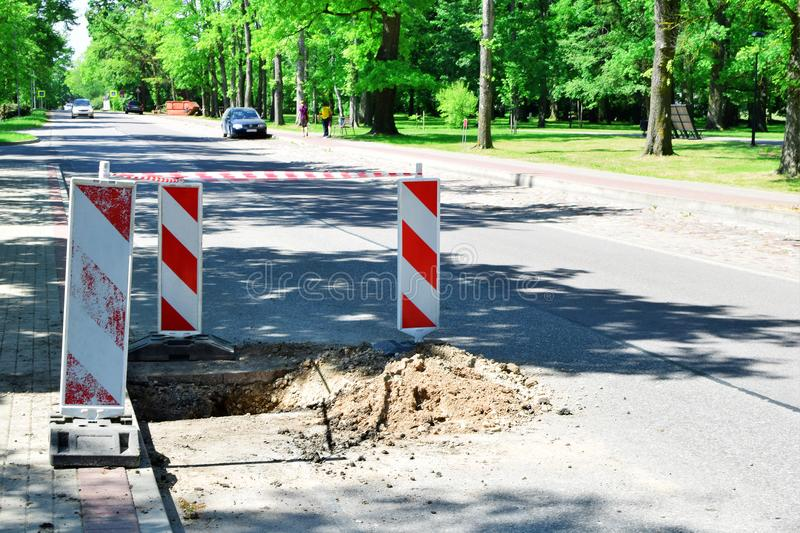 Big pit on road and warning signs royalty free stock photos