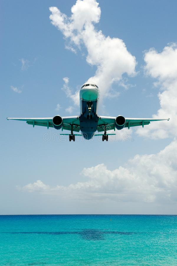 Big plane landing over water royalty free stock photo