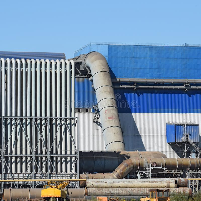 Big plant for processing scrap metal. Huge factory old metal refiner. Blue roof of the factory building. Exhaust pipes, radiators, cooling industrial units as stock images