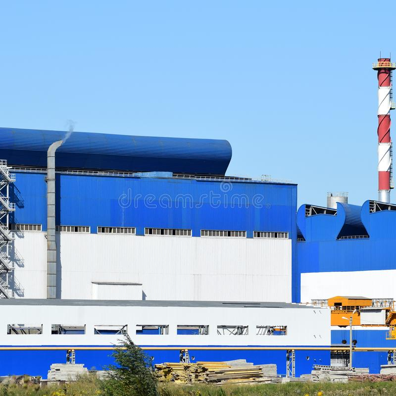 Big plant for processing scrap metal. Huge factory old metal refiner. Blue roof of the factory building. Exhaust pipes, radiators, cooling industrial units as royalty free stock image