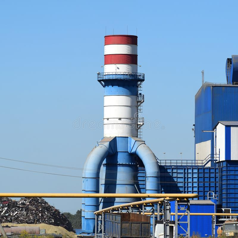 Big plant for processing scrap metal. Huge factory old metal refiner. Blue roof of the factory building. Exhaust pipes, radiators, cooling industrial units as royalty free stock photos