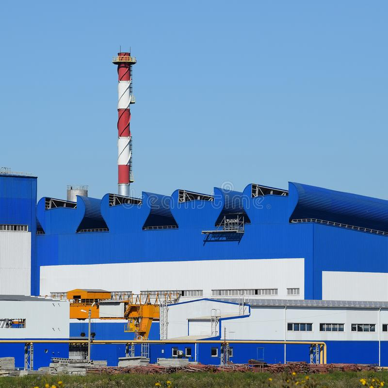 Big plant for processing scrap metal. Huge factory old metal refiner. Blue roof of the factory building. Exhaust pipes, radiators, cooling industrial units as stock photography