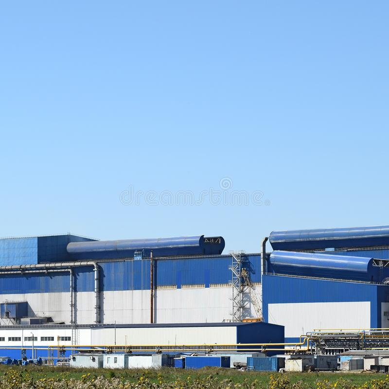 Big plant for processing scrap metal. Huge factory old metal refiner. Blue roof of the factory building. Exhaust pipes, radiators, cooling industrial units as stock photo