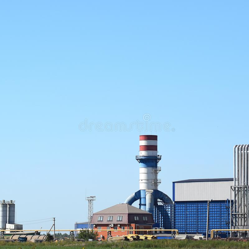 Big plant for processing scrap metal. Huge factory old metal refiner. Blue roof of the factory building. Exhaust pipes, radiators, cooling industrial units as royalty free stock photography