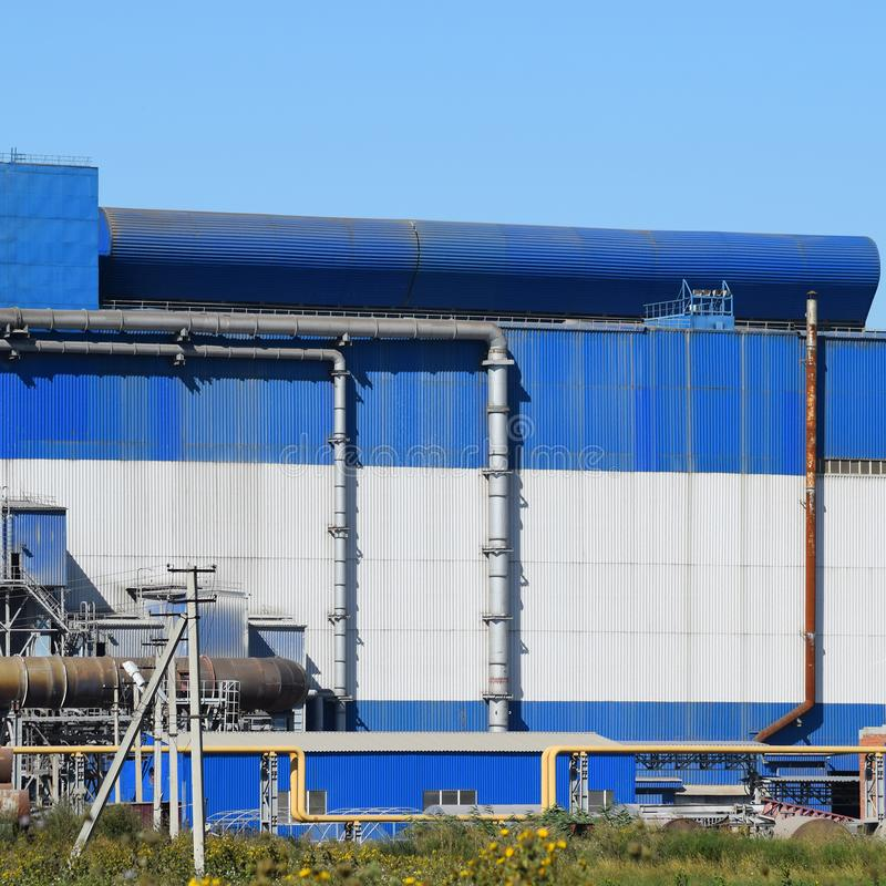 Big plant for processing scrap metal. Huge factory old metal refiner. Blue roof of the factory building. Exhaust pipes, radiators, cooling industrial units as stock image