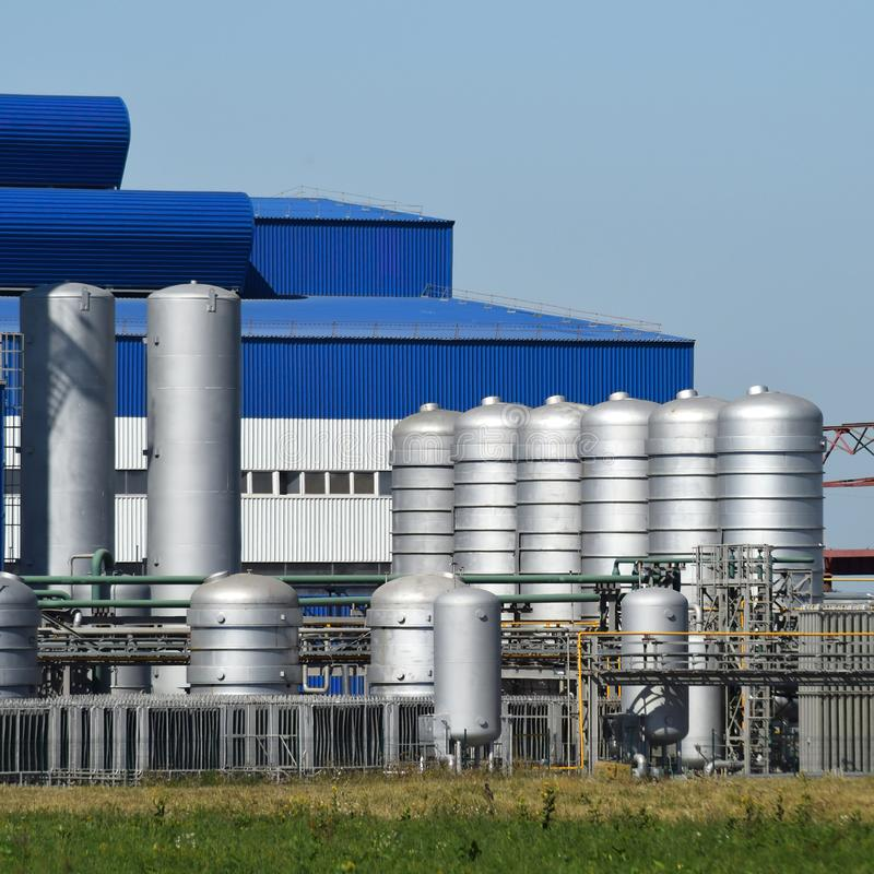 Big plant for processing scrap metal. Huge factory old metal refiner. Blue roof of the factory building. Exhaust pipes, radiators, cooling industrial units as stock photos
