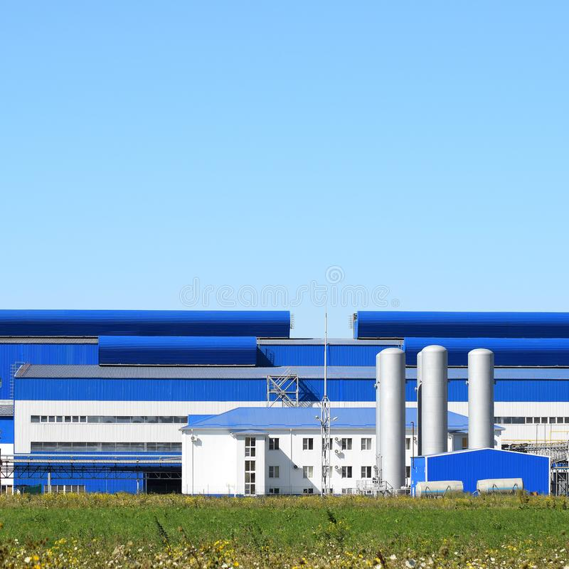 Big plant for processing scrap metal. Huge factory old metal refiner. Blue roof of the factory building. Exhaust pipes, radiators, cooling industrial units as royalty free stock images