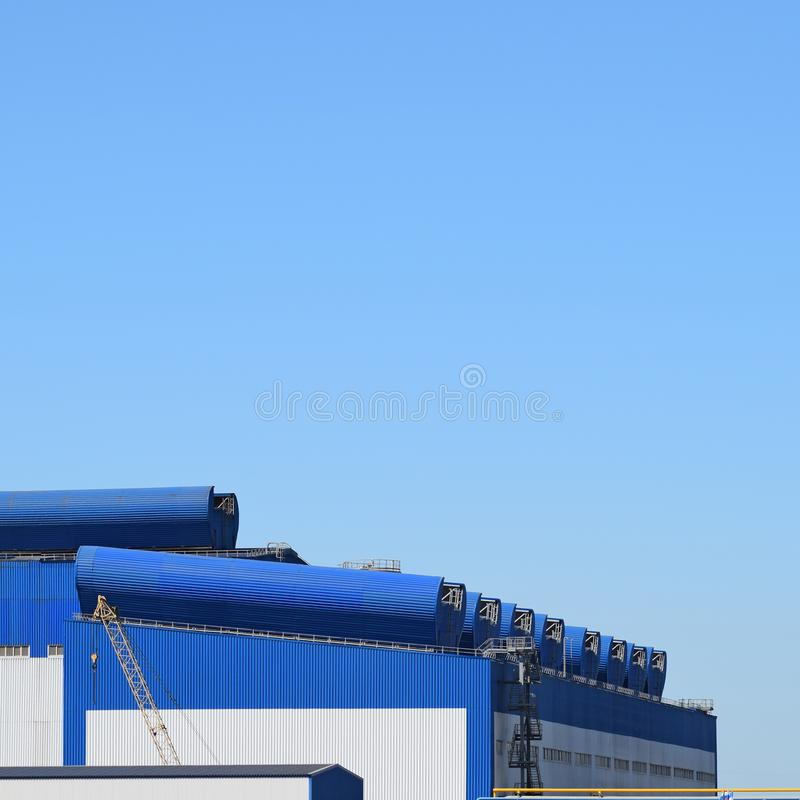 Big plant for processing scrap metal. Huge factory old metal refiner. Blue roof of the factory building. Exhaust pipes, radiators, cooling industrial units as royalty free stock photo
