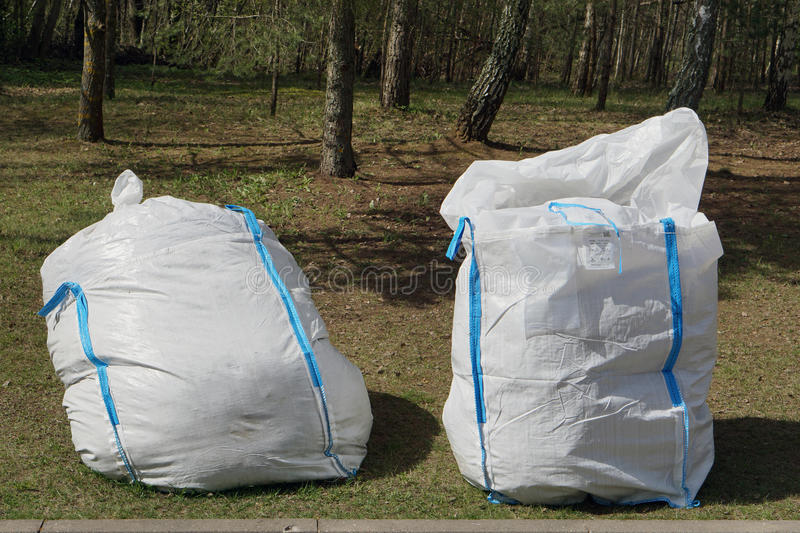 The big plastic bags for branches and leaves. In the wood. Under the European laws - for burning of garbage in the wood or a garden - a penalty of 600 euros stock photos