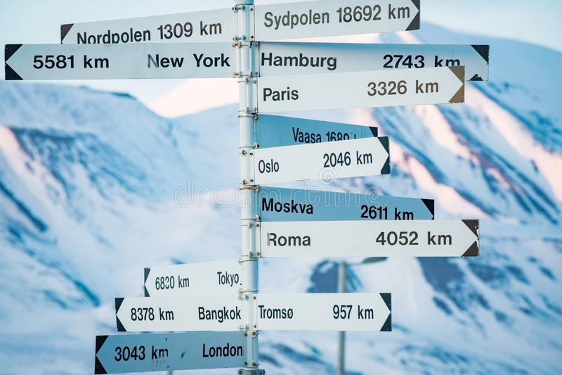 Big pole with directions signs. And distances to cities of the world. Blue sky, mountains covered with snow. Longyearbyen, Spitsbergen, Norway royalty free stock image