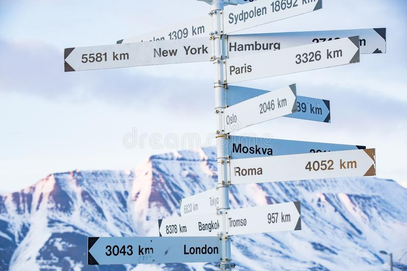 Big pole with directions signs. And distances to cities of the world. Blue sky, mountains covered with snow. Longyearbyen, Spitsbergen, Norway royalty free stock photos