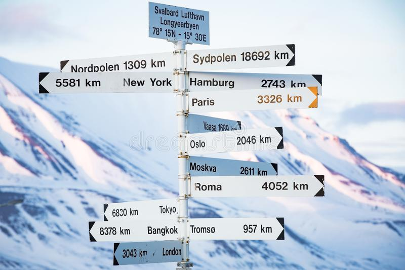 Big pole with directions signs. And distances to cities of the world. Blue sky, mountains covered with snow. Longyearbyen, Spitsbergen, Norway stock image
