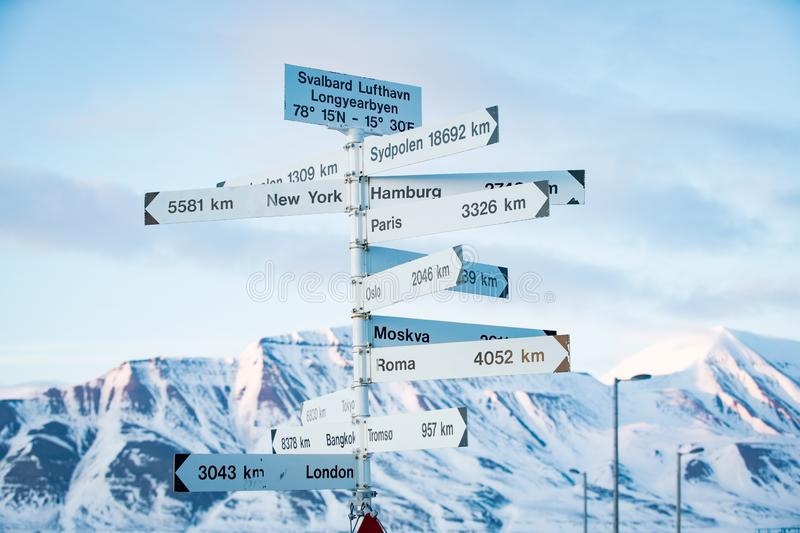 Big pole with directions signs. And distances to cities of the world. Blue sky, mountains covered with snow. Longyearbyen, Spitsbergen, Norway royalty free stock photography
