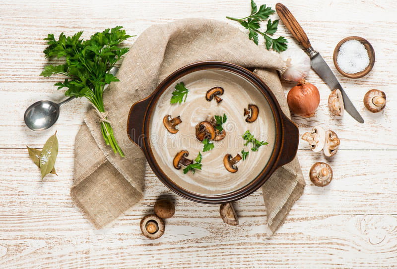 Big pot of soup with mushrooms. Delicious soup puree with champignons in a pot surrounded by scattered fresh mushrooms and ingredients on a rustic wooden table stock photography
