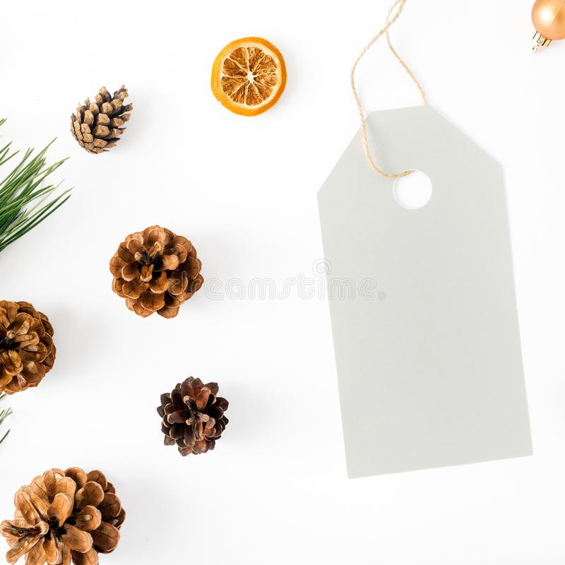 Big price tag with fir branch, cones, orange, Christmas balls. Big price tag with fir branch, pine cones, dry orange and Christmas balls on white background, top stock image