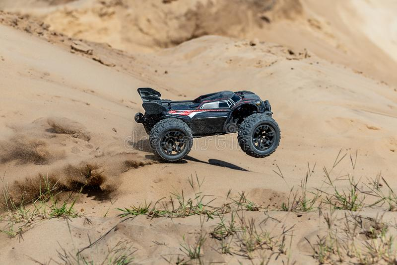 Big radio controlled buggy car driving fast and slipping on sand. RC toy moving fast on cross-terrain surface with dust. And mud outdoors. Children hobby stock photo