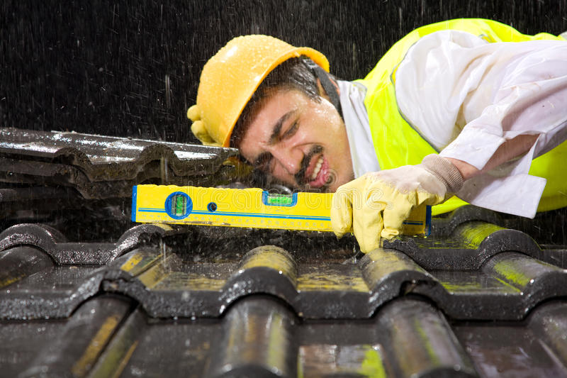 Worker on roof fixing roof tiles. Big rain is falling on black roof tiles royalty free stock photo