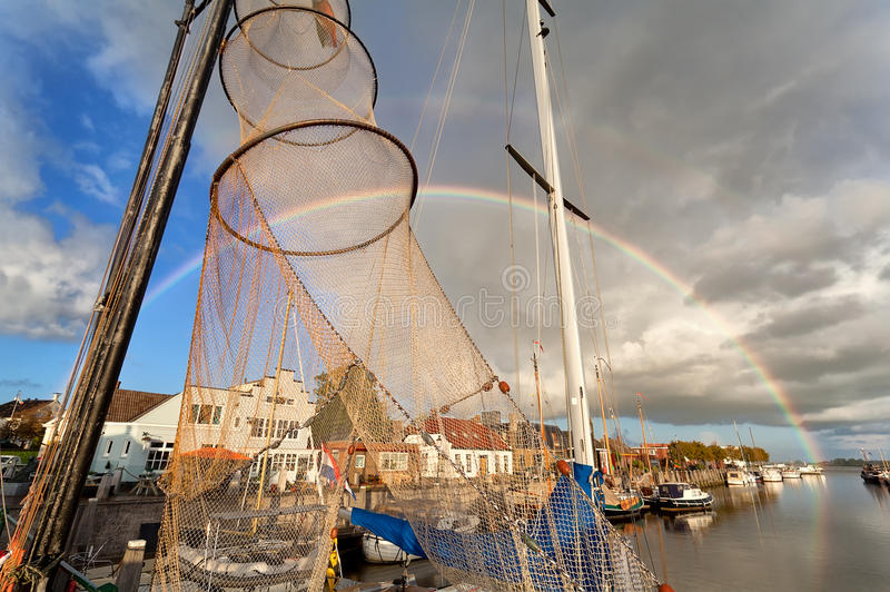 Big rainbow over harbour with fishing boats royalty free stock photography