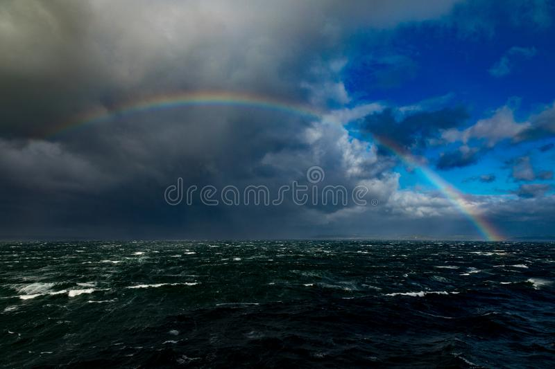 Big Rainbow Over Rough Seas In The English Channel. Rough seas in the English Channel with a colorful rainbow and France in the background. Photo taken from a stock image