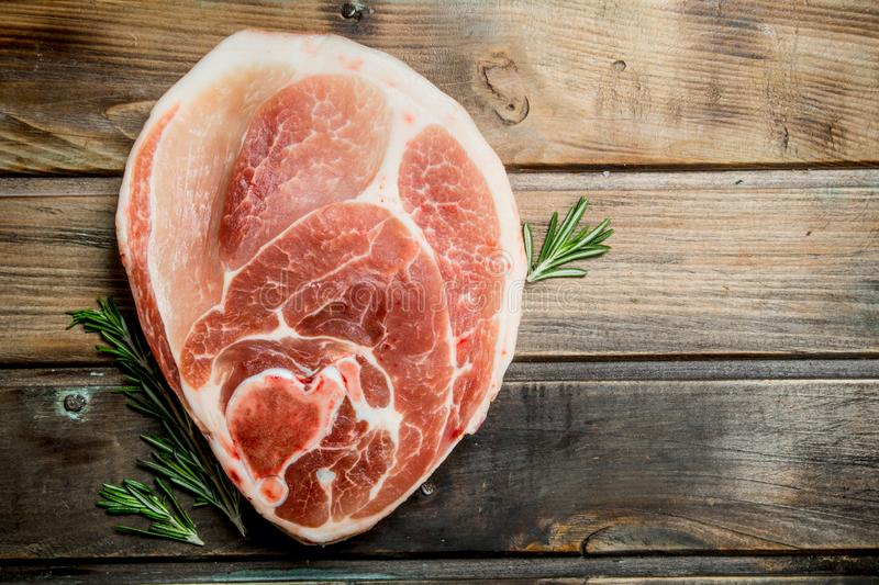 Big raw piece of pork meat with rosemary. On a wooden background royalty free stock image