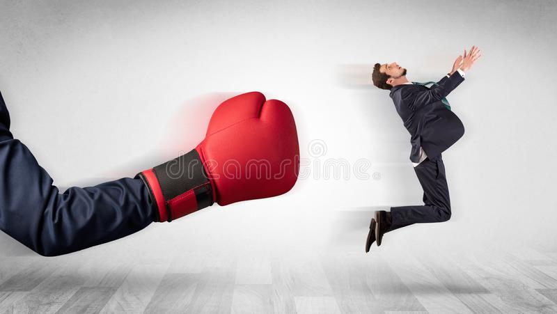 Red boxing glove knocks out little businessman. Big red boxing glove knocks out little businessman conceptn royalty free stock image