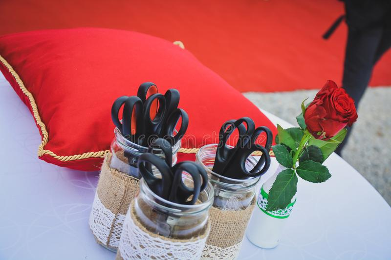 Red cushion and scissors for cutting the ribbon stock images