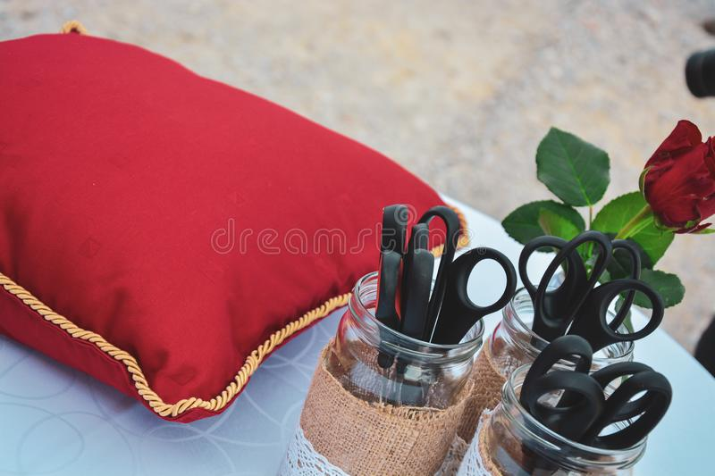 Red cushion and scissors for cutting the ribbon royalty free stock photo