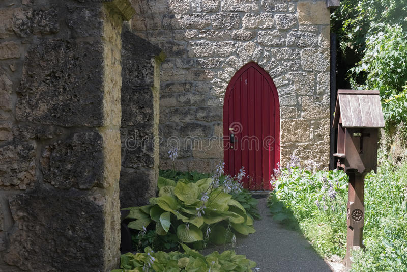 Big red door of an old stone church royalty free stock photo