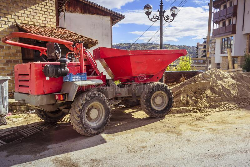 A big red dump truck in front of a building under construction. A big red dump truck in front of a building under construction stock images