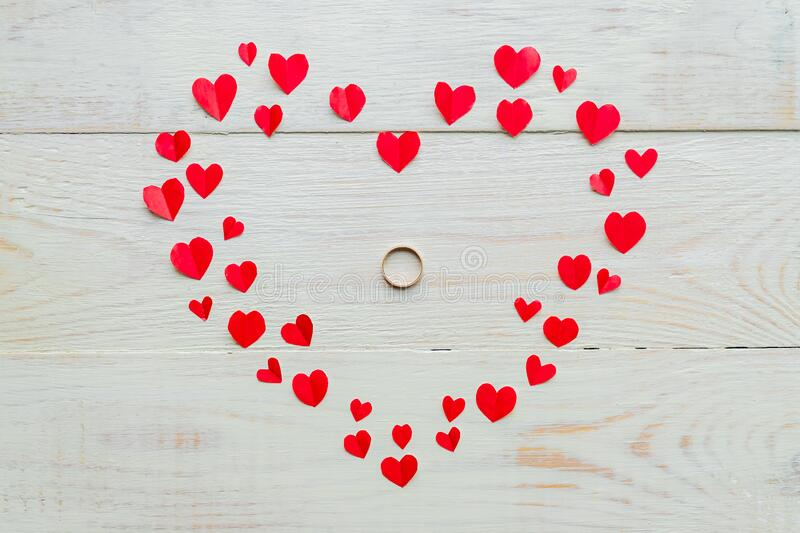 Big red heart made of cut out paper small hearts with wedding ring on wooden backround. Handmaede decoration for Valentine`s day stock images