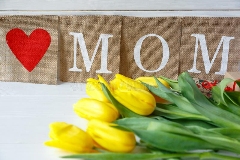 Big red letters Mum lies on the table with gift card and flowers. Mother`s day concept. top view royalty free stock photography