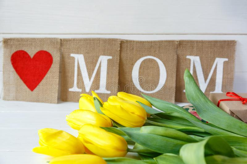 Big red letters Mom lies on the table with gift card and yellow tulips. Flowers for gift. Mother`s day concept. stock images