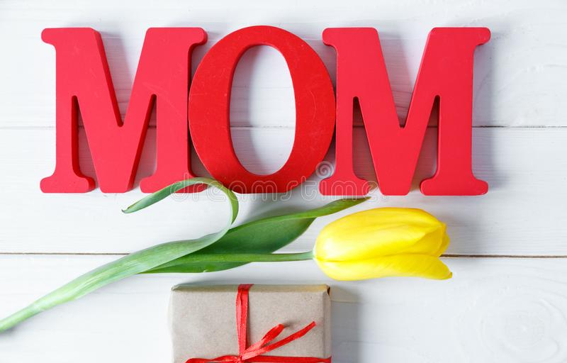 Big red letters Mom lies on the table with gift card and yellow tulips. Flowers for gift. Mother`s day concept. royalty free stock photography