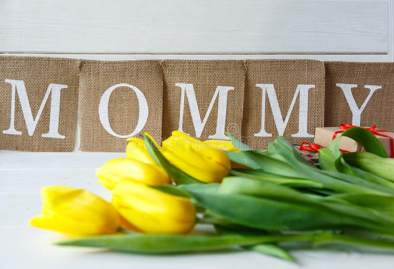 Big red letters Mum lies on the table with gift card and flowers. Mother`s day concept. stock photos