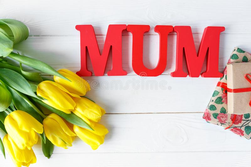 Big red letters Mum lies on the table with gift card and flowers. Mother`s day concept. top view royalty free stock photos