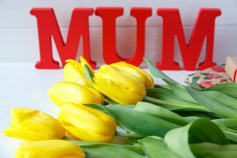 Big red letters Mum lies on the table with gift card and yellow tulips. Flowers for gift. Mother`s day concept. royalty free stock image