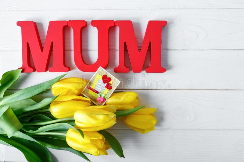 Big red letters Mum lies on the table with gift card and yellow tulips. Flowers for gift. Mother`s day concept. royalty free stock photo