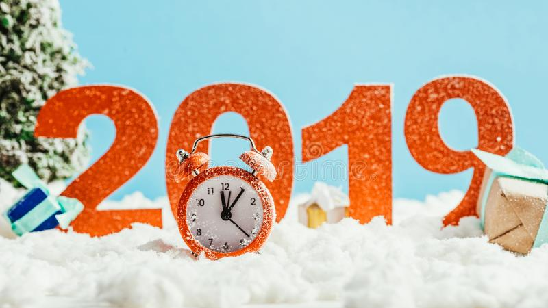 Big red 2019 numbers with vintage alarm clock and gifts on snow. On blue background, new year concept stock photo