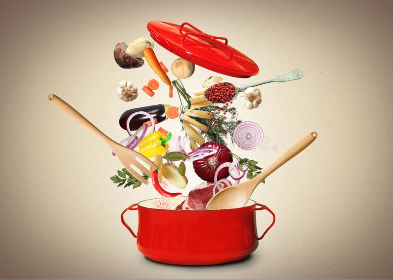 Big red pot for soup. With fork and spoon royalty free stock photo