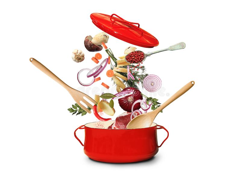 Big red pot for soup. With fork and spoon royalty free stock images