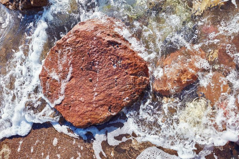 Big red rock in the sea. Surrounded with colorful rocks and water royalty free stock photos
