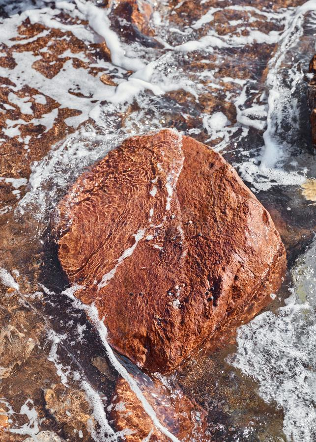 Big red rock in the sea. Big red rock surrounded by splashing waves in the sea royalty free stock photography